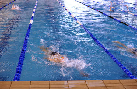 Swimming competition: some teens at the of the lap
