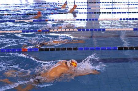 Jongens zwemmen in een zwembad tijdens een schoolslag kampioenschap Stockfoto