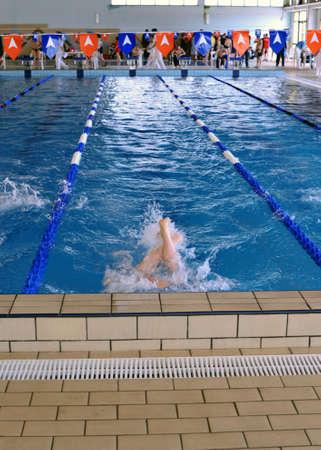 Teen salto tijdens een kampioenschap zwemmen in het zwembad