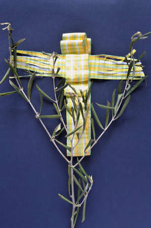 christianity palm sunday: Abstract: decorative ribbon shaped as a crucifix and olive-branch on blue