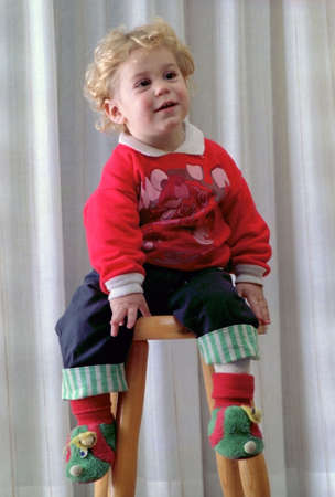 Portrait of attractive blond baby boy acting as poser on a stool photo