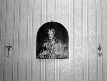 Vintage Christ icon hanging in the bedroom on a wallpapered wall    photo