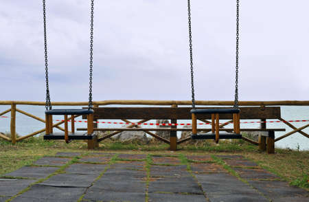 Empty swings in a playground in front of the sea photo