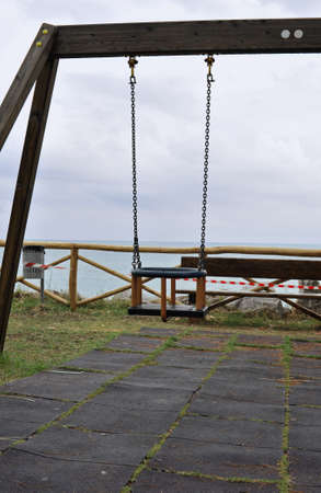 Detail of a swing in a playground in front of the sea  photo