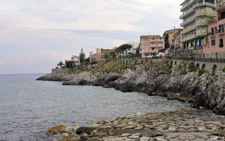 Wide-shot of Marina di Camerota coast with promenade and buildings at sunset photo