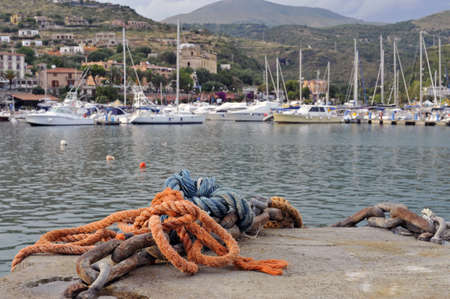 Metal ship mooring and ropes closeup with Marina of Camerota harbor in the background, Italy  photo