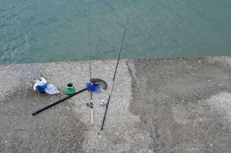 Waiting to catch some fish, lonely fishing-rods on the pier photo