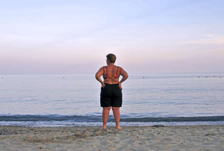 Woman on the shoreline contemplating the horizon at the sunset   photo