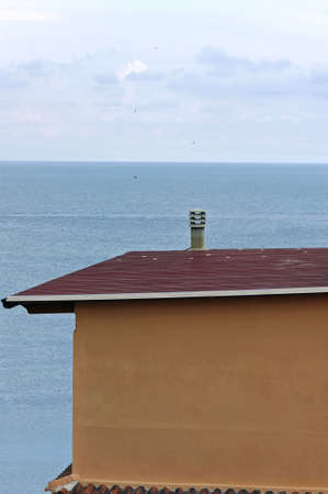 Orange building with red tile roof facing the sea photo