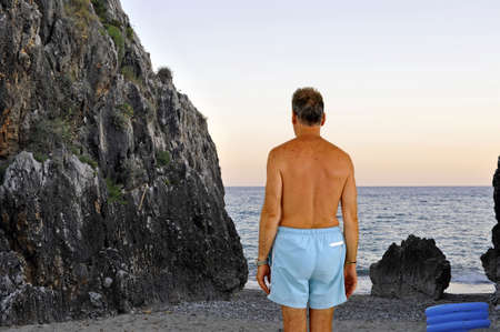 Man with swimming-trunks approaching a boulders on the rocky shoreline Stock Photo - 5517543