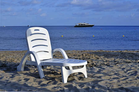 Deckchair on the shoreline with anchored yacht onshore photo