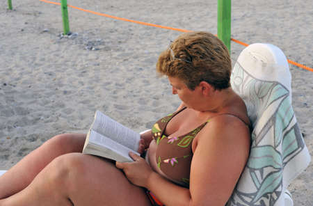 Portrait of a woman reading a book on a deckchair at the beach   photo