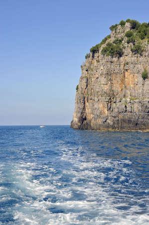 palinuro: Wake of a boat crossing a sheer rock along Palinuro seacoast, Italy