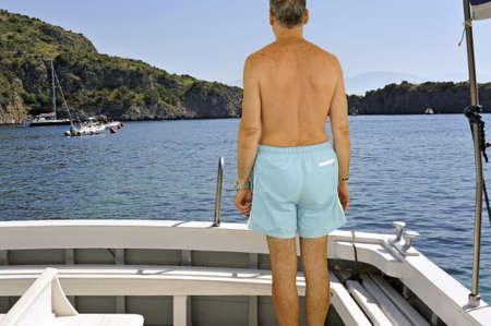 Man looking at the seacoast standing on a yacht stern photo