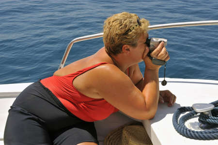 Tourist on a motorboat filming during a summer ride  photo
