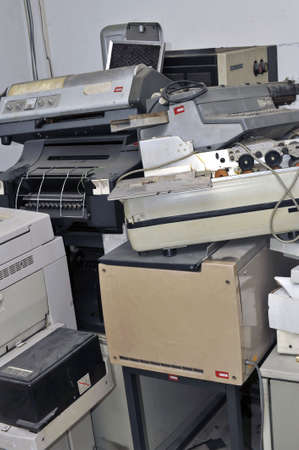 Old abandoned office appliances and equipments piled up in a storeroom photo