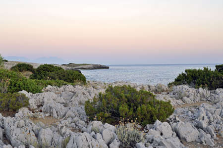 Seascape with eroded rocks at sunset, Camerota coastline, Italy photo