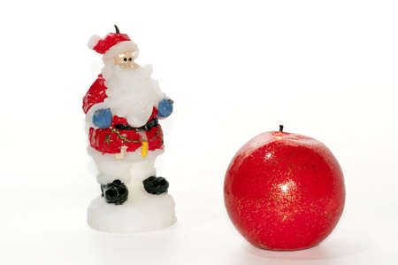 Wax Santa claus figurine and red ball-shaped candle over white Stock Photo - 5936184
