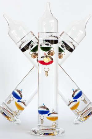 Three water Galileo thermometers with colorful globes in liquid photo