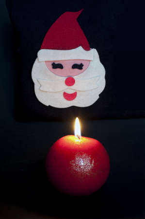 Fabric Santa claus figurine with ball-shaped lighted up candle on black background photo