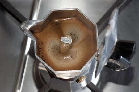 Italian moka on burning gas while discharging coffee, focus on the coffee photo