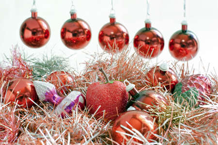 Hanging red Christmas balls and tinsel with different baubles  photo