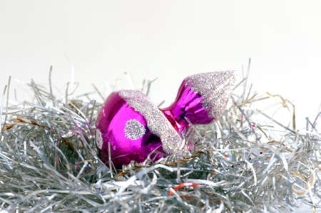 gewgaw: Close-up of a shiny pink Christmas bauble on a silver tinsel