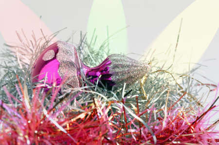 gewgaw: Christmas bauble on tinsel with colored spotlight in the background   Stock Photo