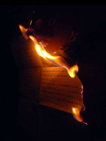 Abstract: a paper sheet with love message while burning isolated on black photo