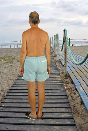 Man on a beach boardwalk to the seaside resort at the sunset photo