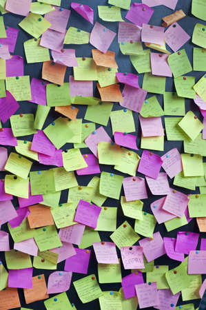 """Post it notes with handwritten messages about """"invisibility"""" hung with pushpins on a bulletin board  Stock Photo"""