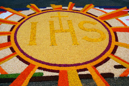liturgical: Spello, Umbria, Italy - May 2010: Christogram made by fresh petals on the pavement for the floral decorations contest called �Infiorata of Spello�. Annual liturgical event held in the street on the Sunday after Corpus Domini in Spello, Italy