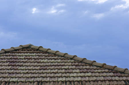 A tile roof against a clouded blue sky photo