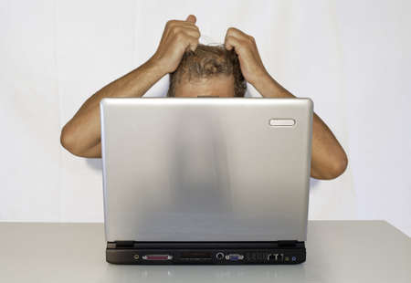 Conceptual: an exasperated man in front of a laptop (in horizontal) Stock Photo - 7556087
