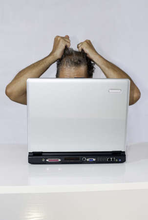 Conceptual: an exasperated man in front of a laptop (in vertical)