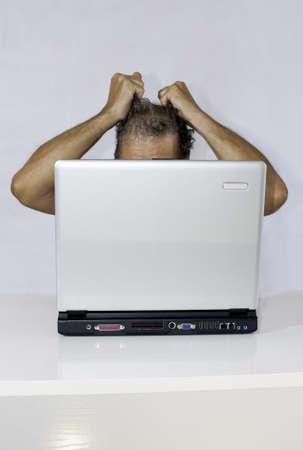Conceptual: een verbitterd man voor een laptop (in verticaal) Stockfoto