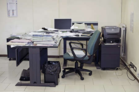 Lonely office room with messy desk filled up with documents  photo