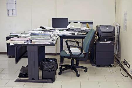 messy desk: Sala de oficina solitaria con escritorio desordenado rellenado con documentos