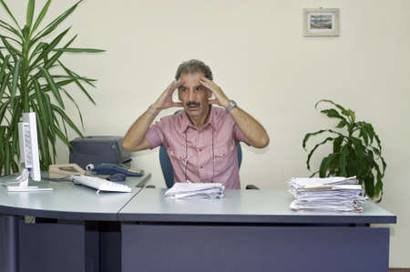 outwork: Discouraged manager man at his desk in the office Stock Photo