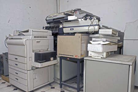 Oude afgedankte office toestellen en uitrusting opgestapeld in een berging Stockfoto