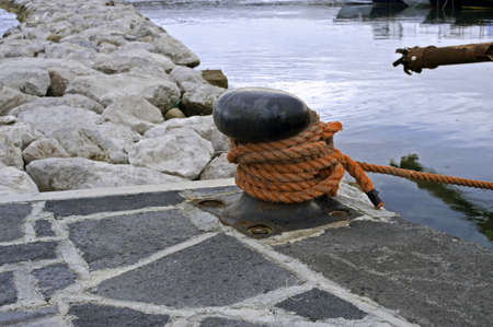 Closeup of a metal mooring bollard with rope on the pier head Stock Photo - 7632447