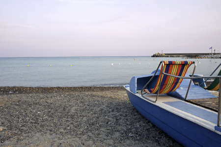 Vacant beach at dusk with paddle boat inshore photo