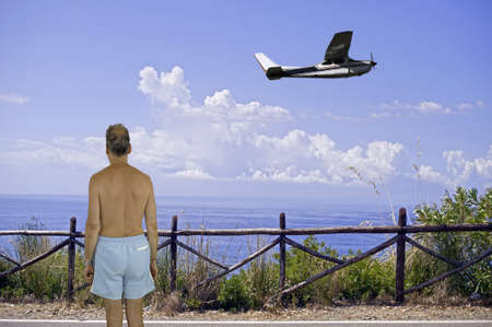stockade: Man in trunks near a stockade facing the seacoast with an airplane flying aloft Stock Photo