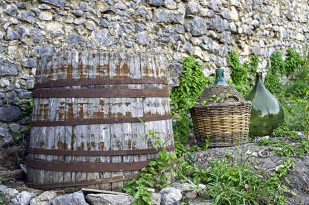 Rural scene with old wood barrel and some glass demijohn for wine photo