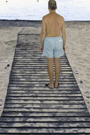 Man in trunks on a beach boardwalk to the seaside resort at the sunset Stock Photo - 7917454
