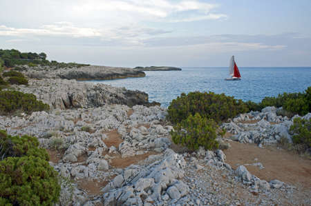 Picturesque isle coastline with a sailboat against the horizon in the evening, Salerno, Italy Stock Photo - 7928928