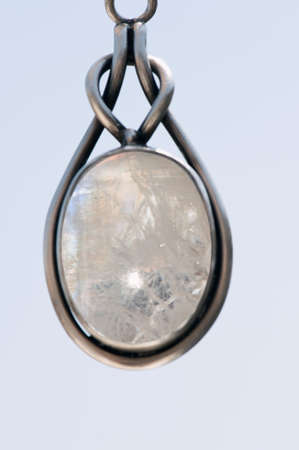 Closeup of a silver pendant with a moon stone gem-set