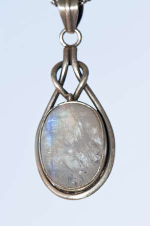 Closeup of a silver pendant with a moon stone gem-set  photo