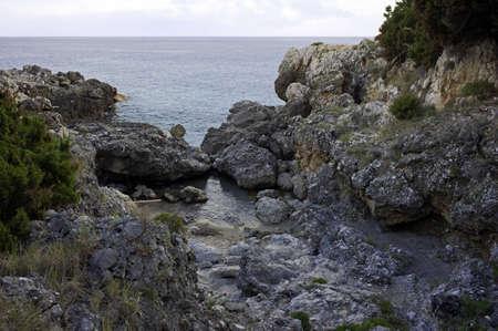 Rocky small nook along the jagged coastline, Cilento, Italy photo