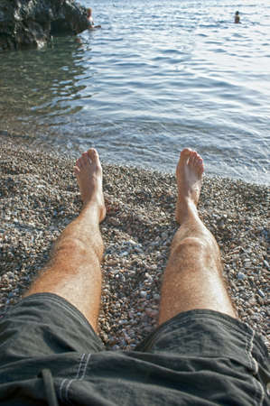 Man legs stretched out on the shoreline at the beach photo